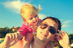 Daughter sat on father shoulders. Royalty Free Stock Photos