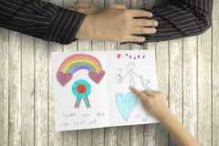 Daughter saying thank you to father with card. Top view of little daughter saying thank you to her father with hand painting on greeting card, wooden background Royalty Free Stock Photos