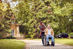 Daughter and senior man in wheelchair on walking green nature. Caring daughter and senior men in wheelchair on walking green nature Royalty Free Stock Image