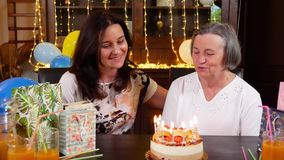 Daughter and senior mother blowing candles on birthday cake or Mothers Day party. Pan of young daughter and senior mother blowing candles on birthday cake at