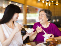 Daughter and senior mother enjoy eating in restaurant. Happy daughter and senior mother enjoy eating in restaurant Royalty Free Stock Photos