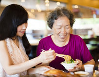 Daughter and senior mother enjoy eating in restaurant Royalty Free Stock Photos