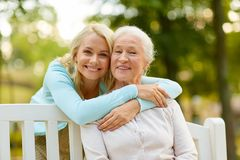 Daughter with senior mother hugging on park bench. Family, generation and people concept - happy smiling young daughter with senior mother sitting on park bench royalty free stock photography