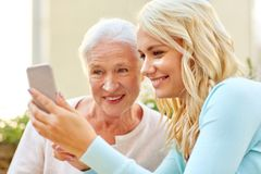 Daughter and senior mother with smartphone outdoor royalty free stock photo