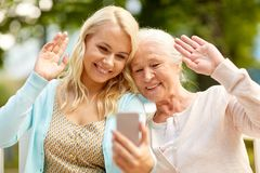 Daughter and senior mother taking selfie at park Royalty Free Stock Photography