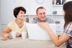 Daughter showing documents on laptop to her senior parents. Adult daughter showing documents on laptop to her senior parents at home royalty free stock photo