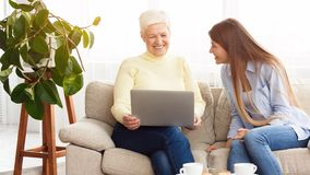 Daughter showing mother funny videos on laptop. Having rest at home royalty free stock photo