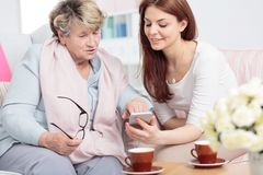 Daughter showing smartphone to senior woman while drinking tea royalty free stock photo