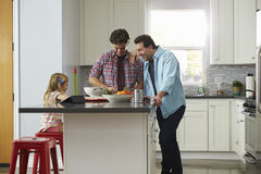 Daughter sits in kitchen while her male parents prepare meal Stock Photo
