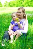 Daughter sits on mother on a grass outdoors. With a dandelion Stock Photos