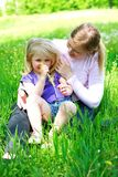 Daughter sits on mother on a grass outdoors. Smiling Stock Photo