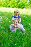 Daughter sits on mother on a grass outdoors Stock Image