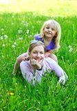 Daughter sits on mother on a grass outdoors. Smiling Stock Photography