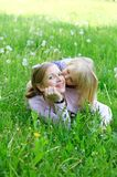 Daughter sits on mother on a grass outdoors Royalty Free Stock Images