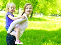 Daughter sits on mother on a grass outdoors. With a dandelion Stock Images