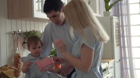 The daughter sits on the table, the parents stand nearby. Mom opens the teapot, daughter looks into the teapot. Happy family in the kitchen, where the daughter stock video