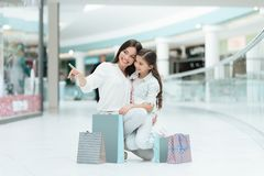 Daughter is sitting on mother`s lap in shopping mall. Mom and girl are smiling. stock images