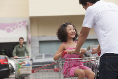 Daughter sitting in shopping cart and father pushing, outdoors in front of supermarket Stock Photography