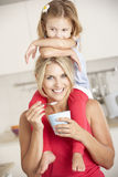 Daughter Sitting On Shoulders Whilst Mother Eats Yoghurt Royalty Free Stock Images