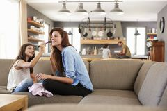 Daughter Sitting On Sofa At Putting Make Up On Mother stock images