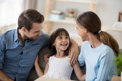 Daughter sitting together with parents on couch in living room stock images