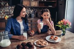 Daughter and mother eating cupcakes royalty free stock photos