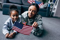 Daughter and soldier with american flag. African american daughter and soldier in military uniform with american flag at home royalty free stock photography