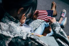 Daughter and soldier with american flag. Back view of african american daughter and female soldier in military uniform with american flag at home royalty free stock photos