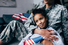Daughter and soldier with american flag. Cropped view of african american daughter and female soldier in military uniform with american flag at home royalty free stock image
