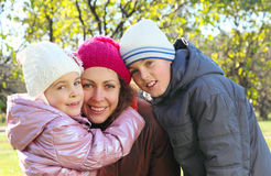 Daughter, son hug mother in autumn forest Stock Images
