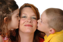 Daughter and son kissing mom. Against a white background royalty free stock photo