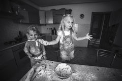 Daughter and son mess up with flour on kitchen Stock Photos