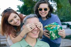 Daughter and son suprise dad covering eyes to give a gift. Conce. Teen daughter and son suprise dad covering eyes to give a gift. Concept of family, happiness stock photos