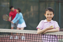 daughter standing next to the tennis net, parents playing in the background Stock Photography