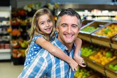 Daughter staying on her fathers back Stock Photography
