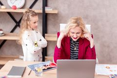 Unpleasant blonde mother plugging her ears with fingers. Daughter staying nearby. Unpleasant blonde mother plugging her ears with fingers while little girl stock photography