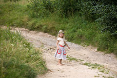 Daughter of summer. Little girl in wild flowers wreath standing on road barefoot stock photo