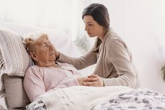 Daughter supporting sick mother lying in hospital bed stock image