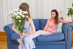 Daughter surprising mother with flowers Stock Photo