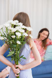 Daughter surprising mother with flowers Stock Images