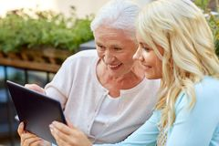 Daughter with tablet pc and senior mother outdoors. Family, technology and people concept - happy smiling young daughter with tablet pc computer and senior royalty free stock photography