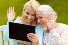 Daughter with tablet pc and senior mother at park Royalty Free Stock Photo