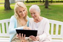 Daughter with tablet pc and senior mother at park Royalty Free Stock Image