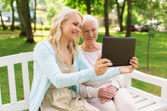 Daughter with tablet pc and senior mother at park Stock Photography