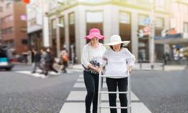 Daughter take care elderly woman walking across the street. Daughter take care elderly women walking across the street in downtown Stock Images