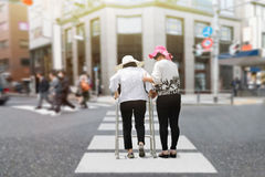 Daughter take care elderly woman walking across street. Daughter take care elderly women walking across street in strong sun light stock photography