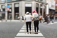 Daughter take care elderly woman walking on street. Daughter take care elderly women walking on street in downtown Royalty Free Stock Photo