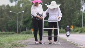 Daughter take care elderly woman walking on street.