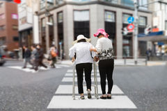 Daughter take care elderly woman walking on street. Daughter take care elderly women walking on street in downtown Royalty Free Stock Images