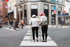 Daughter take care elderly woman walking on street. Royalty Free Stock Images